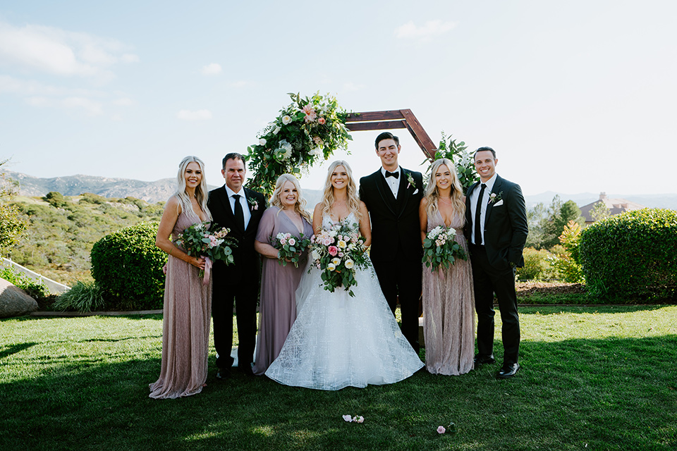 bride in a white ballgown with a strapless neckline and a long veil and the groom in a notch lapel tuxedo and black bow tie, the bridesmaids in rose gold long gowns and the groomsmen in black tuxedos with black long ties