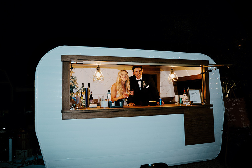 bride in a white ballgown with a strapless neckline and a long veil and the groom in a notch lapel tuxedo and black bow tie, in a trailer mobile bar