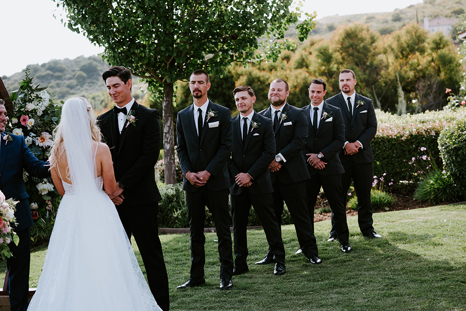 bride in a white ballgown with a strapless neckline and a long veil and the groom in a notch lapel tuxedo and black bow tie, the groomsmen in black tuxedos with black long ties at the ceremony