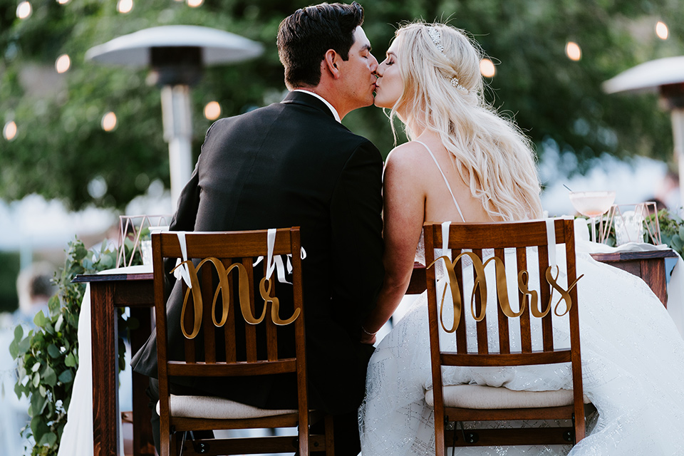 bride in a white ballgown with a strapless neckline and a long veil and the groom in a notch lapel tuxedo and black bow tie, at the reception in their chairs