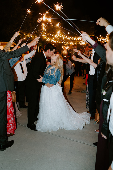 bride in a white ballgown with a strapless neckline and a long veil and jean jacket, and the groom in a notch lapel tuxedo and black bow tie kissing with the sparklers