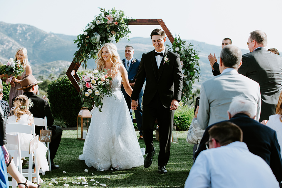 bride in a white ballgown with a strapless neckline and a long veil and the groom in a notch lapel tuxedo and black bow tie, walking down the aisle