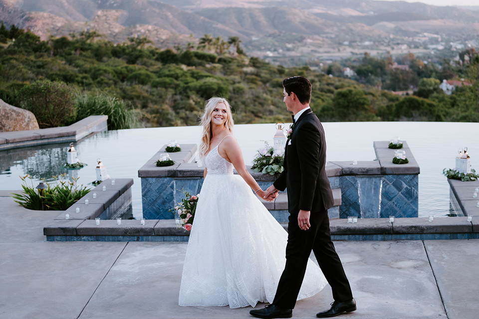 bride in a white ballgown with a strapless neckline and a long veil and the groom in a notch lapel tuxedo and black bow tie, walking by the pool