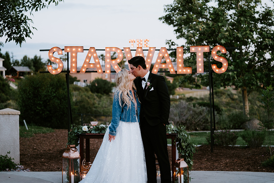 bride in a white ballgown with a strapless neckline and a long veil and a jean jacket, and the groom in a notch lapel tuxedo and black bow tie, kissing next to marquee lights