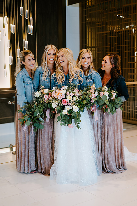 bride in a white ballgown with a strapless neckline and a long veil and jean jacket, and her bridesmaids in rose gold gowns and jean jackets