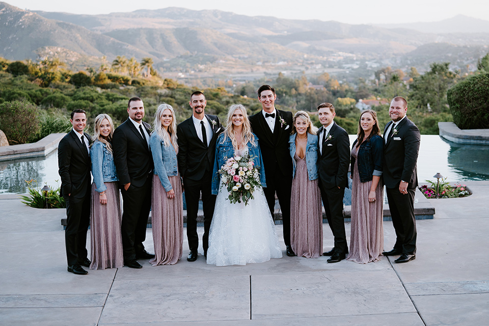 bride in a white ballgown with a strapless neckline and a long veil and jean jacket, the groom in a notch lapel tuxedo and black bow tie, the bridesmaids in rose gold long gowns and jean jackets, and the groomsmen in black tuxedos with black long ties