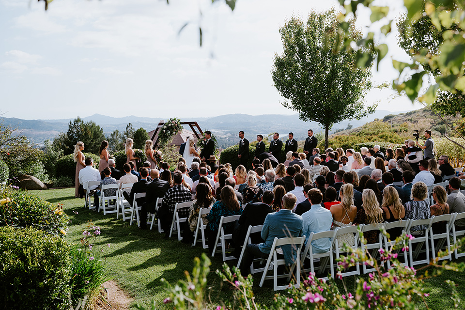 bride in a white ballgown with a strapless neckline and a long veil and jean jacket, the groom in a notch lapel tuxedo and black bow tie, the bridesmaids in rose gold long gowns and jean jackets, and the groomsmen in black tuxedos with black long ties at the ceremony