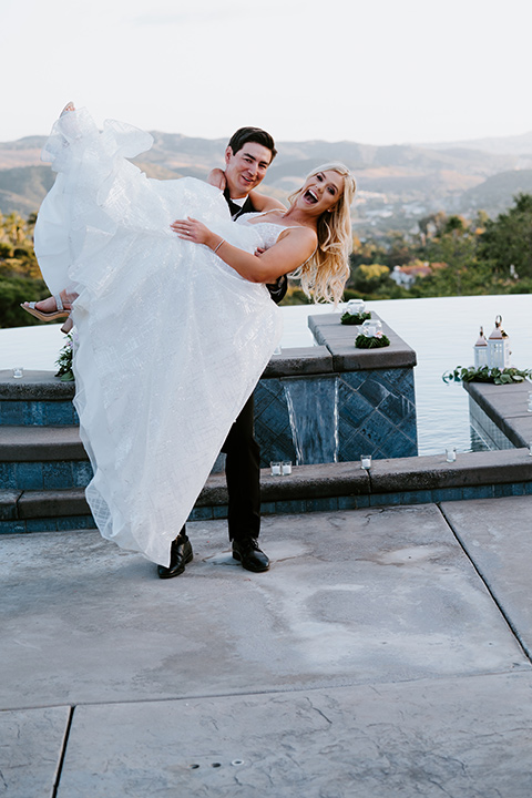 bride in a white ballgown with a strapless neckline and a long veil and the groom in a notch lapel tuxedo and black bow tie dancing