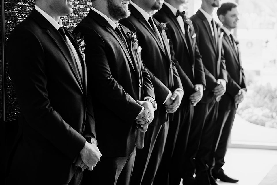 groom and groomsmen in black tuxedos with black bow ties