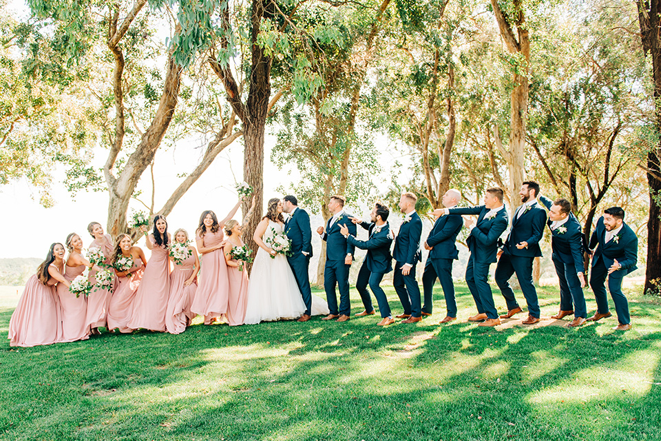 bride in a white ball gown with train and the groom in a dark blue suit in bow tie, bridesmaids in blush gowns and the groomsmen in dark blue suits