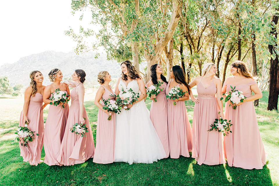 bride in a white ball gown with train and the bridesmaids in blush pink gowns