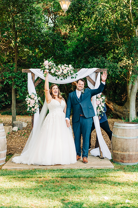 bride in a white ball gown with train and the groom in a dark blue suit in bow tie at ceremony