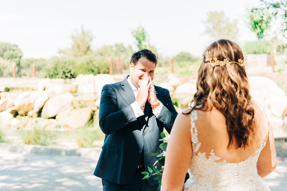 bride in a white ball gown with train and the groom in a dark blue suit in bow tie
