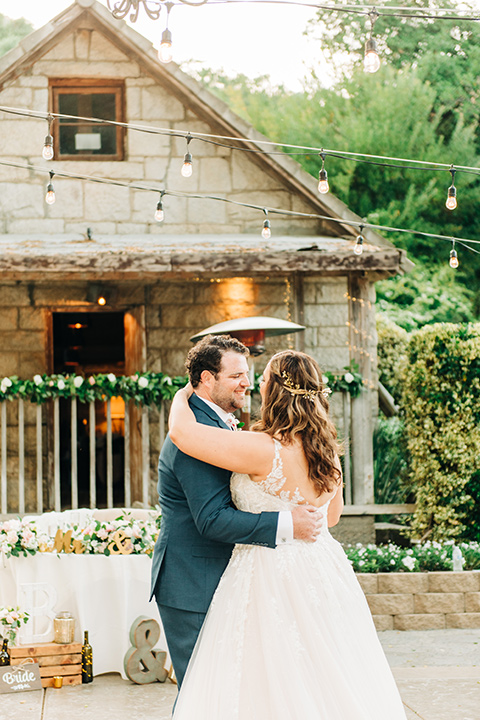 bride in a white ball gown with train and the groom in a dark blue suit in bow tie first dance