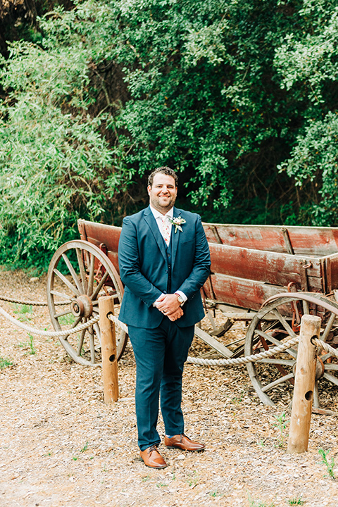 groom in a dark blue suit and bow tie