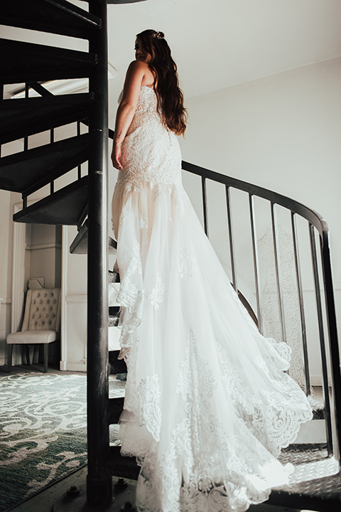 bride in a formfitting white lace gown with a long train