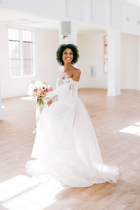 bride in a tulle ballgown with an off the shoulder detail and full billowed sleeves