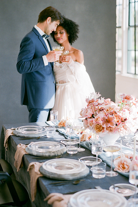 bride in a tulle ballgown with an off the shoulder detail and full billowed sleeves and the groom in a slate blue suit with a matching bow tie at the end of the table