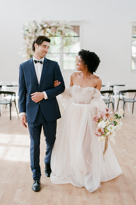 bride in a tulle ballgown with an off the shoulder detail and full billowed sleeves walking away from the altar together