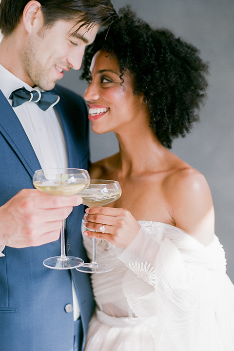 bride in a tulle ballgown with an off the shoulder detail and full billowed sleeves holding cocktail glasses