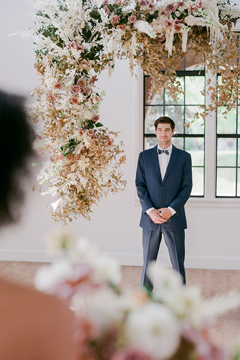 bride in a tulle ballgown with an off the shoulder detail and full billowed sleeves and the groom in a slate blue suit with a matching bow tie waiting at the end of the altar for bride