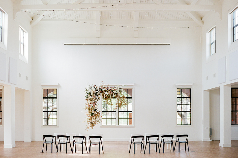 white ceremony décor with black chairs and soft floral arrangements