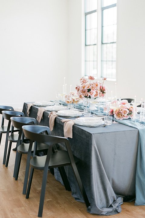 dusty blue linens with tall candles and blush toned florals