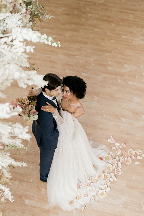 bride in a tulle ballgown with an off the shoulder detail and full billowed sleeves and the groom in a slate blue suit with a matching bow tie dancing