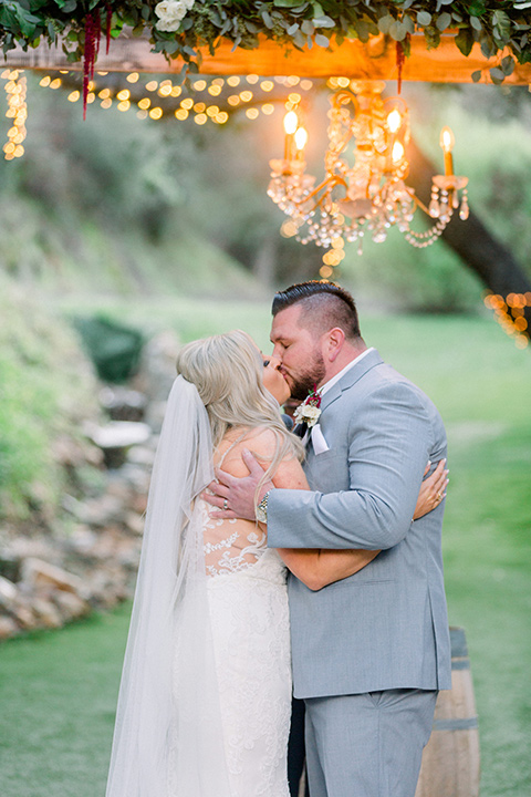 bride in a white lace mermaid style gown and a strapless neckline and groom in a light grey suit at the ceremony