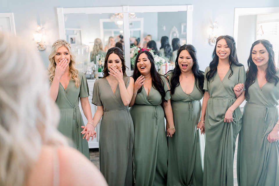 bride in a mermaid style lace white gown and the bridesmaids in sage green dresses