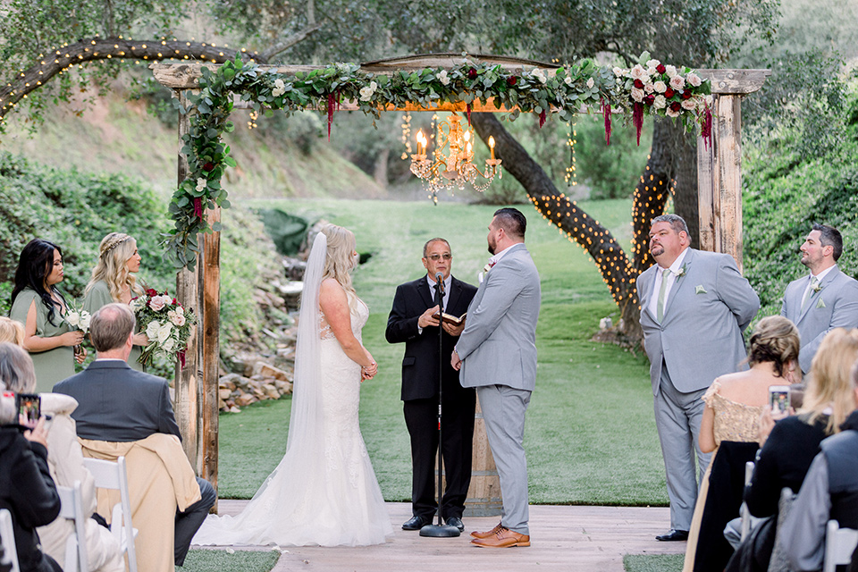 bride in a mermaid style lace white gown and the groom in a light grey suit with a light brown shoes and white pocket square, the bridesmaids in sage green dresses and the groomsmen in light grey suits and bow ties
