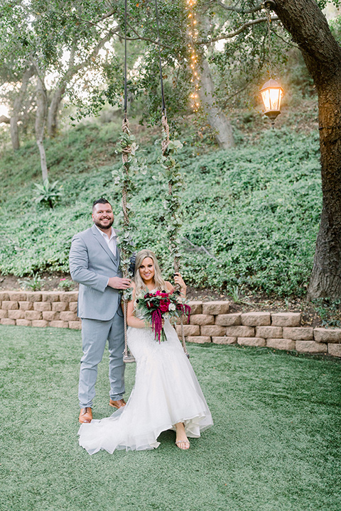 bride in a white lace mermaid style gown and a strapless neckline and the groom in a light grey suit on a tree swing