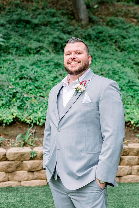 groom in a light grey suit on a tree swing