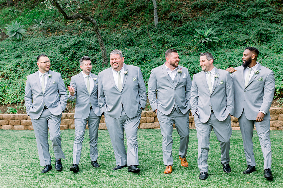 groom in a light grey suit with a light brown shoes and the groomsmen in light grey suits and bow ties