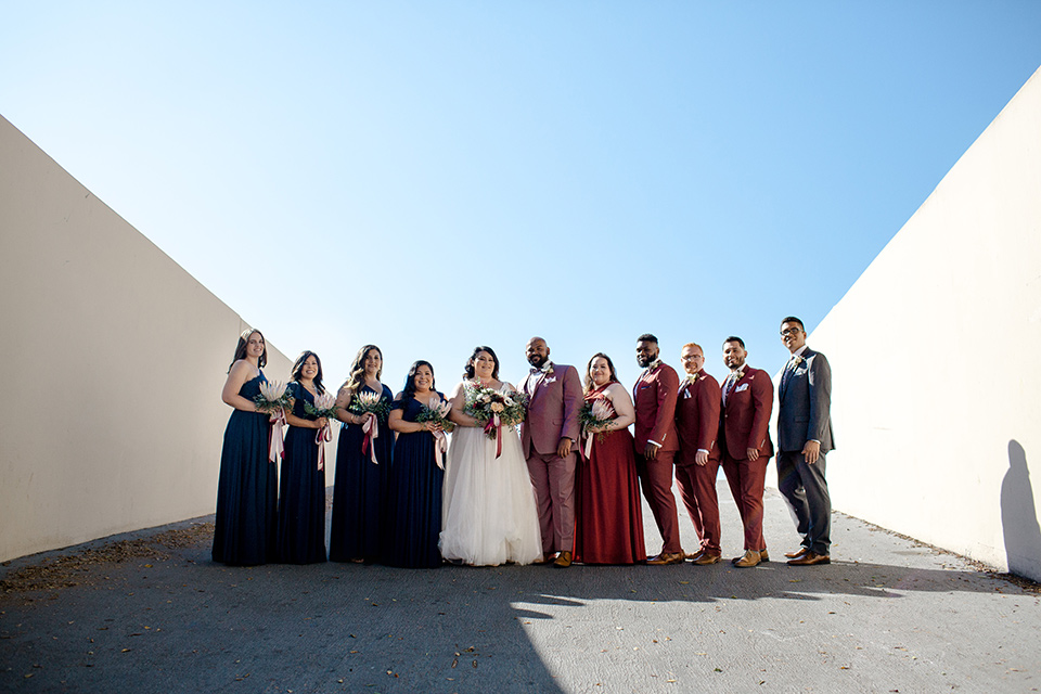 bride in a tulle ballgown with cap sleeves and the groom in a rose pink suit, the groomsmen in burgundy suits and the bridesmaids in black gowns