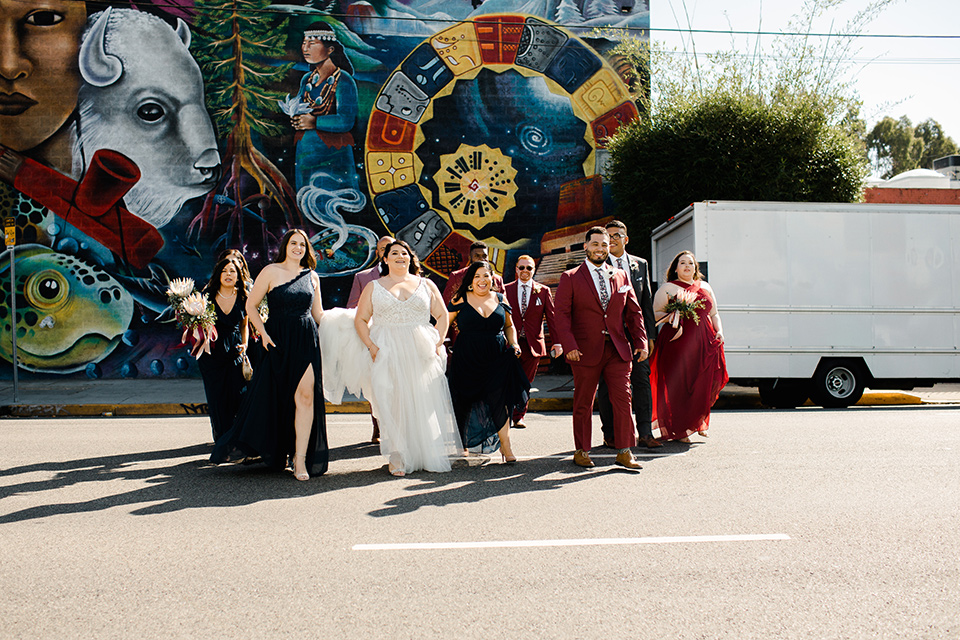 bride in a tulle ballgown with cap sleeves and the groom in a rose pink suit, the groomsmen in burgundy suits and the bridesmaids in black gowns, walking across the street