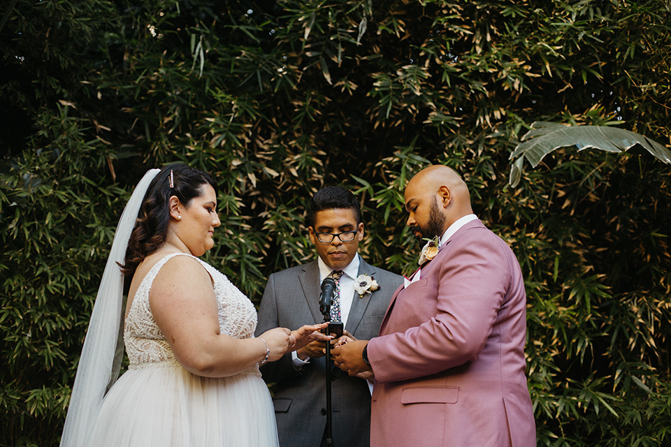 bride in a tulle ballgown with cap sleeves and the groom in a rose pink suit at the ceremony