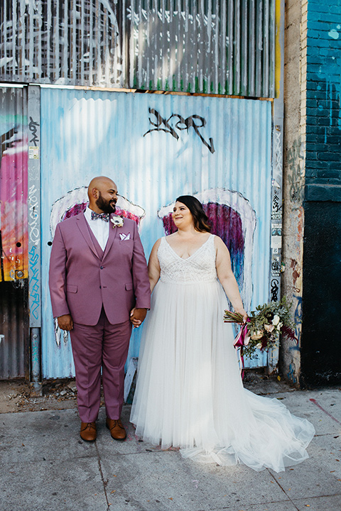 bride in a tulle ballgown with cap sleeves and the groom in a rose pink suit