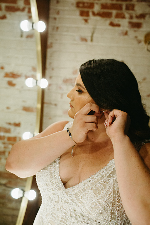 bride in a tulle ballgown with cap sleeves putting on her earrings