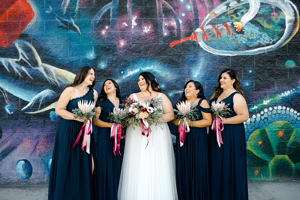 bride in a tulle ballgown with cap sleeves and the bridesmaids in black long gowns