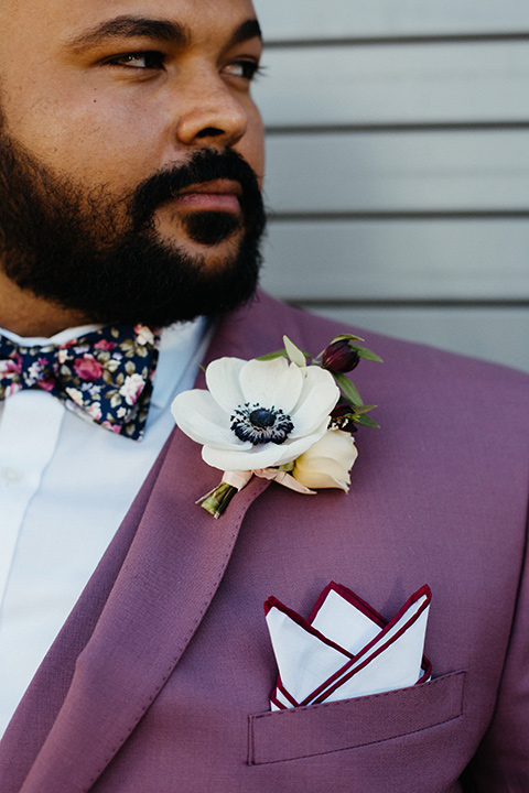 groom in a rose suit with a floral bow tie