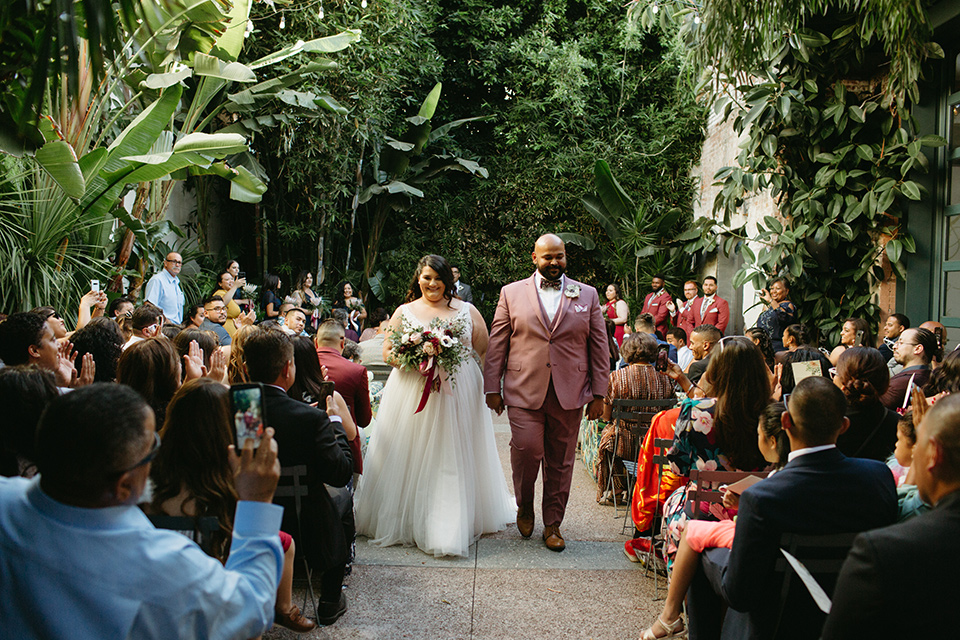 bride in a tulle ballgown with cap sleeves and the groom in a rose pink suit walking down the aisle at the ceremony