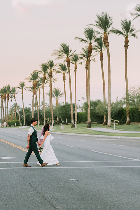 bride in a white bohemian gown with one sleeve and a ruffled detail the groom in a green suit with a white shirt and bolo tie