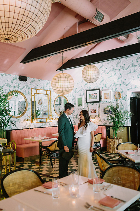 bride in a white bohemian gown with one sleeve and a ruffled detail with a pink veil and the groom in a green suit with a white shirt, bolo tie, and wide brimmed hat in an eccentric pink and mustard colored room with fun paintings on the wall