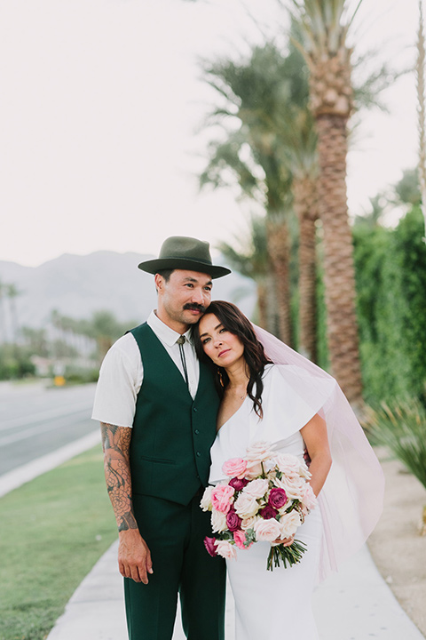 bride in a white bohemian gown with one sleeve and a ruffled detail with a pink veil and the groom in a green suit with a white shirt, bolo tie, and wide brimmed hat