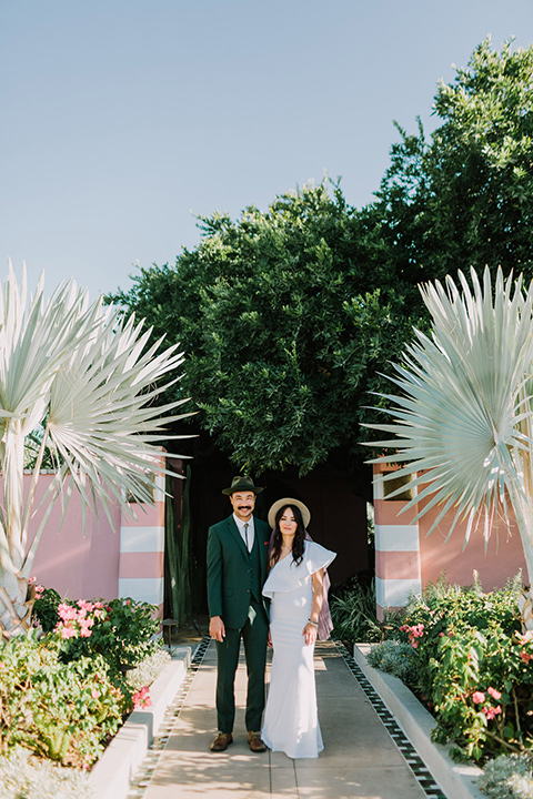 bride in a white bohemian gown with one sleeve and a ruffled detail with a pink veil and the groom in a green suit with a white shirt, bolo tie, and wide brimmed hat looking at camera outside venue