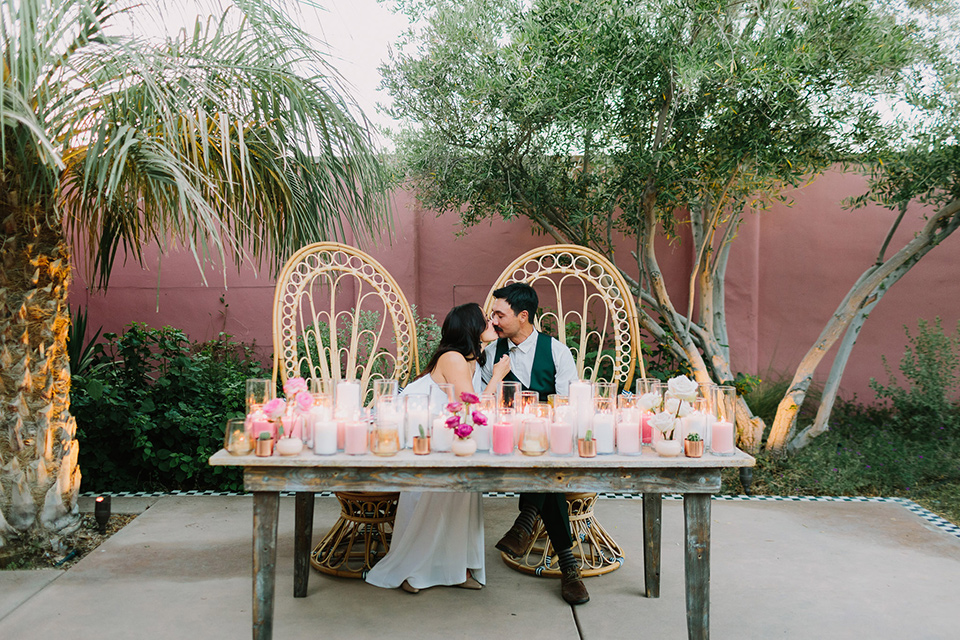 wooden table with boho wicker chairs and pink and green décor on the table