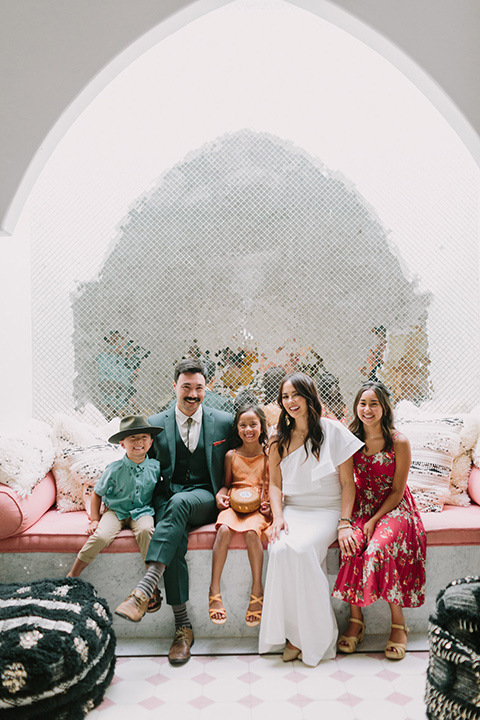 bride in a white bohemian gown with one sleeve and a ruffled detail the groom in a green suit with a white shirt and bolo tie sitting inside with their children around them