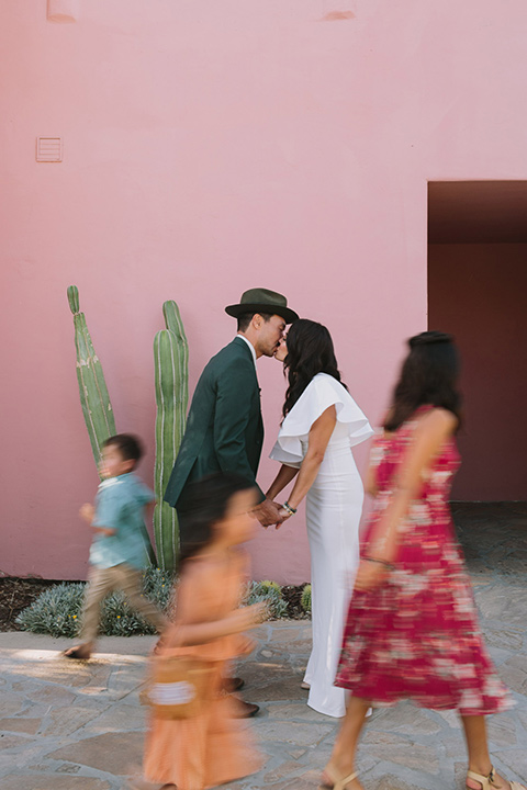 bride in a white bohemian gown with one sleeve and a ruffled detail with a pink veil and the groom in a green suit with a white shirt, bolo tie, and wide brimmed hat kissing with their children running around them