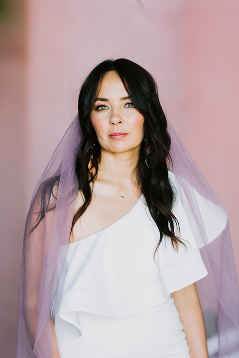 bride in a white bohemian gown with one sleeve and a ruffled detail with a pink veil